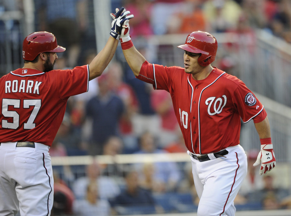 Photo - Washington Nationals' Wilson Ramos, right, gets  high five from Tanner Roark (57) after Ramos hit a home run during the second inning of a baseball game against the Baltimore Orioles, Monday, Aug. 4, 2014, in Washington. (AP Photo/Nick Wass)