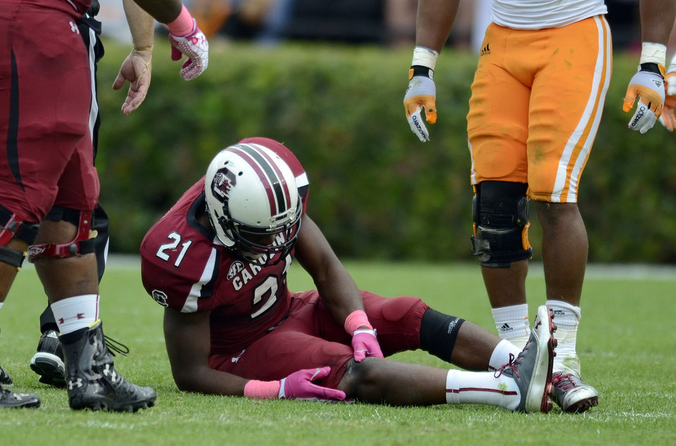 Photo -   South Carolina running back Marcus Lattimore grabs his right knee after getting hit by Tennessee's Eric Gordon during the first half of an NCAA college football game Saturday, Oct. 27, 2012 at Williams-Brice Stadium in Columbia, S.C. (AP Photo/Richard Shiro)