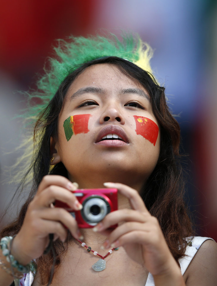 <p>A fan with the flags of Portugal and China on her face takes pictures from the stands during the Euro 2012 soccer championship Group B match between Denmark and Portugal in Lviv, Ukraine, Wednesday, June 13, 2012. (AP Photo/Armando Franca)</p>