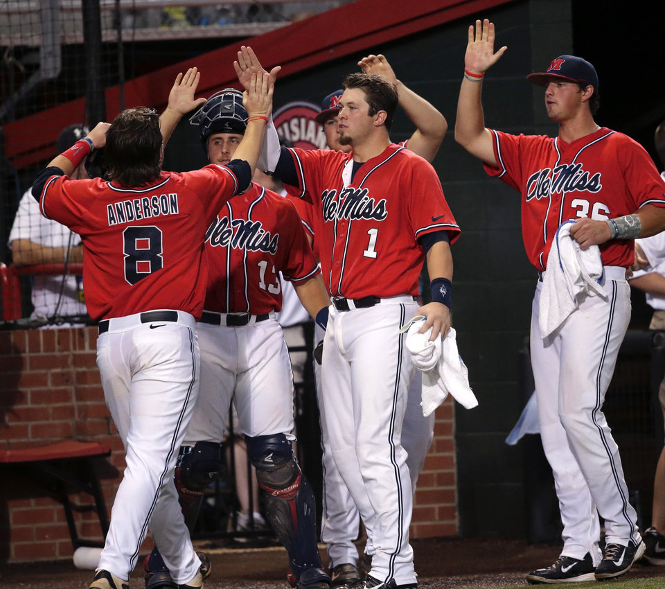 Photo - Mississippi infielder Austin Anderson (8) is greeted at the dugout after scoring on an RBI double by Will Allen in the first inning of an NCAA college baseball tournament super regional game against Louisiana Lafayette in Lafayette, La.,Sunday, June 8, 2014. (AP Photo/Gerald Herbert)