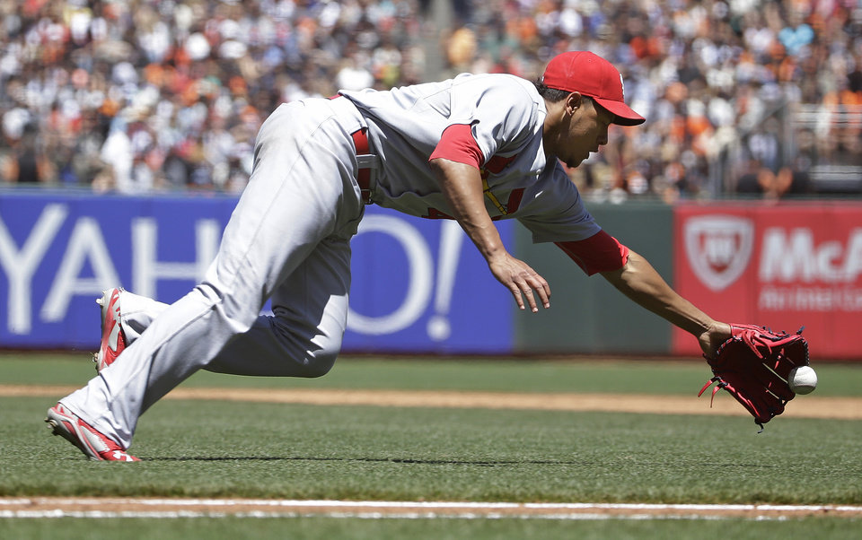 Photo - St. Louis Cardinals starting pitcher Carlos Martinez dives for a bunt ground ball hit by the San Francisco Giants' Gregor Blanco in the fifth inning of their baseball game Thursday, July 3, 2014, in San Francisco. Blanco got a single on the play. (AP Photo/Eric Risberg)