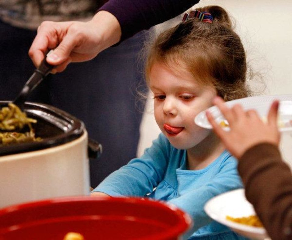 Lily Banz, 3, licks her lips as she goes through the serving line with her mom, Kim Banz, of Oklahoma City. PHOTO BY JIM BECKEL, THE OKLAHOMAN <strong>JIM BECKEL - THE OKLAHOMAN</strong>