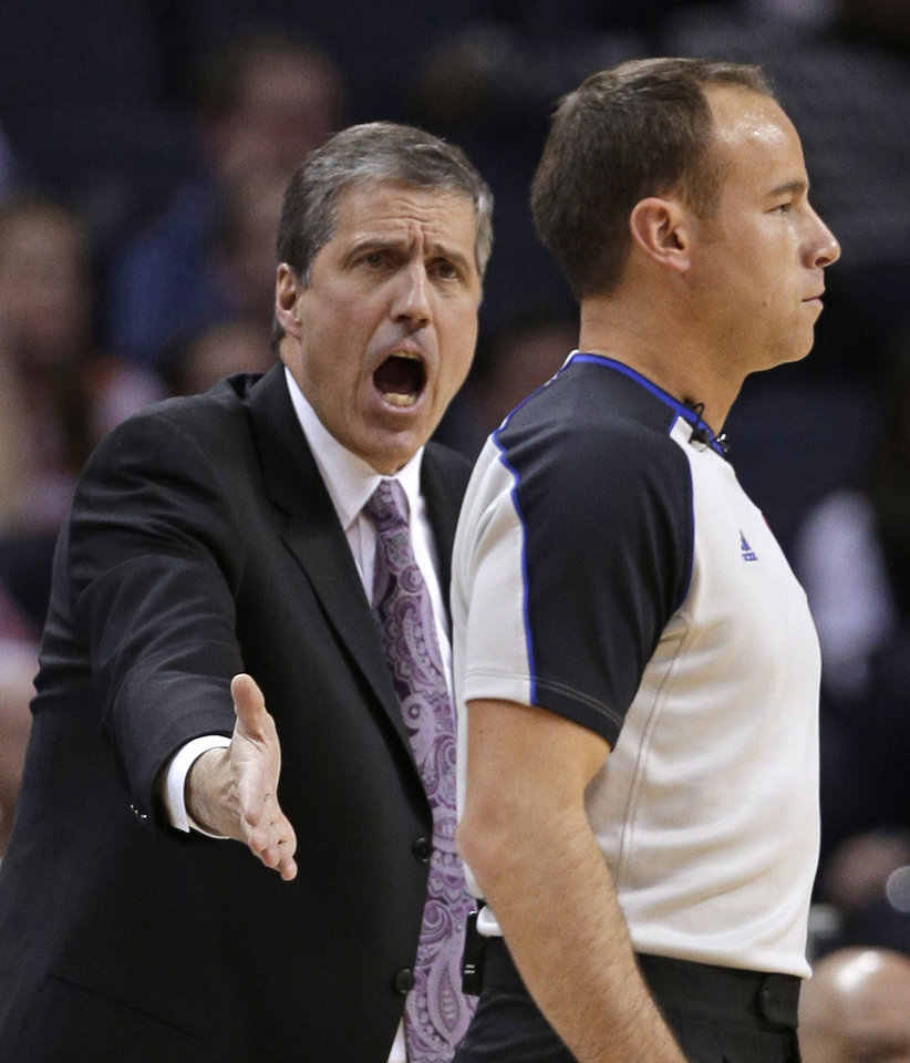 Photo - Washington Wizards coach Randy Wittman, left, argues a call with referee Josh Tiven during the first half of an NBA basketball game against the Charlotte Bobcats in Charlotte, N.C., Tuesday, Jan. 7, 2014. (AP Photo/Chuck Burton)