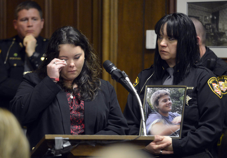 Photo - Crystal King, sister of Russell King, wipes a tear as she addresses the court at the sentencing of T. J. Lane Tuesday, March 19, 2013, in Chardon, Ohio. Lane, was given three lifetime prison sentences without the possibility of parole Tuesday for opening fire last year in a high school cafeteria in a rampage that left three students dead and three others wounded.  King was one of three students killed.  Lane, 18, had pleaded guilty last month to shooting at students in February 2012 at Chardon High School, east of Cleveland.  (AP Photo/The News-Herald, Duncan Scott, Pool)