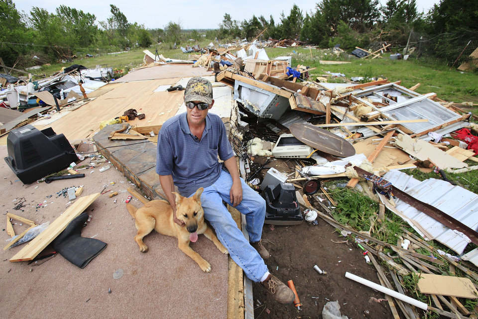Photo - Charles Taylor, 37, sits with his dog, Sissy, Wednesday afternoon, May 12, 2010, on the hearth in what was his living room before a tornado destroyed his mobile home near Earlsboro in Pottawatomie County, Monday night.  Taylor was not inside his home when the twister hit; he was in his truck headed to his house when he decided he needed to turn around to find shelter, but not before he found himself trapped in his truck as the tornado went past.  He was not injured. He came home to find all that remains of his home is the foundation.    Photo by Jim Beckel, The Oklahoman