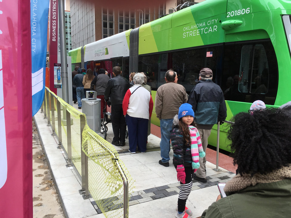 Photo - Lines formed downtown on Friday morning to catch the first rides on the Oklahoma City Streetcar after the grand opening ceremony on the east plaza at Leadership Square. Hundreds of people filled the plaza for a children's choir and brass band, speeches, elders' stories about riding the original trolley system, and blasts of confetti. [The Oklahoman]