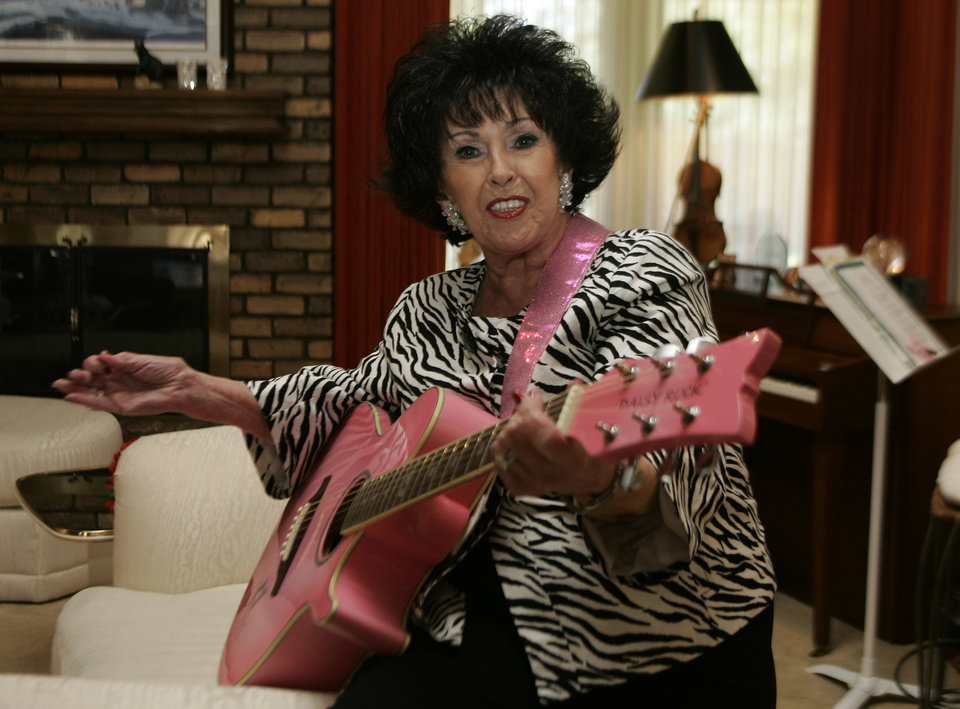 Photo - In this photo shot Tuesday, May 19, 2009, Wanda Jackson plays a song for the photographer in her home in Oklahoma City. (AP Photo/Sue Ogrocki) ORG XMIT: OKSO103