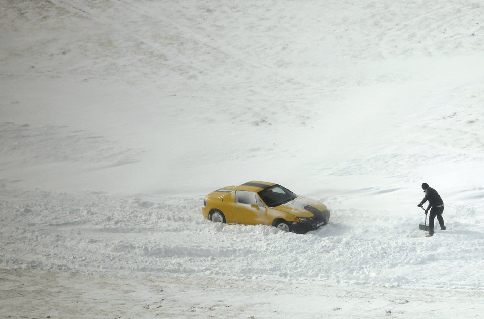 Photo - A motorist tries to dig a path for their car on the access road to I-235 near Britton Road during a major winter storm that hit central Oklahoma Tuesday, Feb. 1, 2011. Photo by Doug Hoke, The Oklahoman.