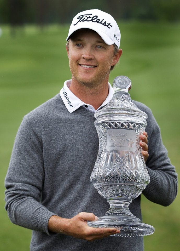 Photo - Matt Jones holds the championship trophy after winning the Houston Open golf tournament on Sunday, April 6, 2014, in Humble, Texas. (AP Photo/Patric Schneider)