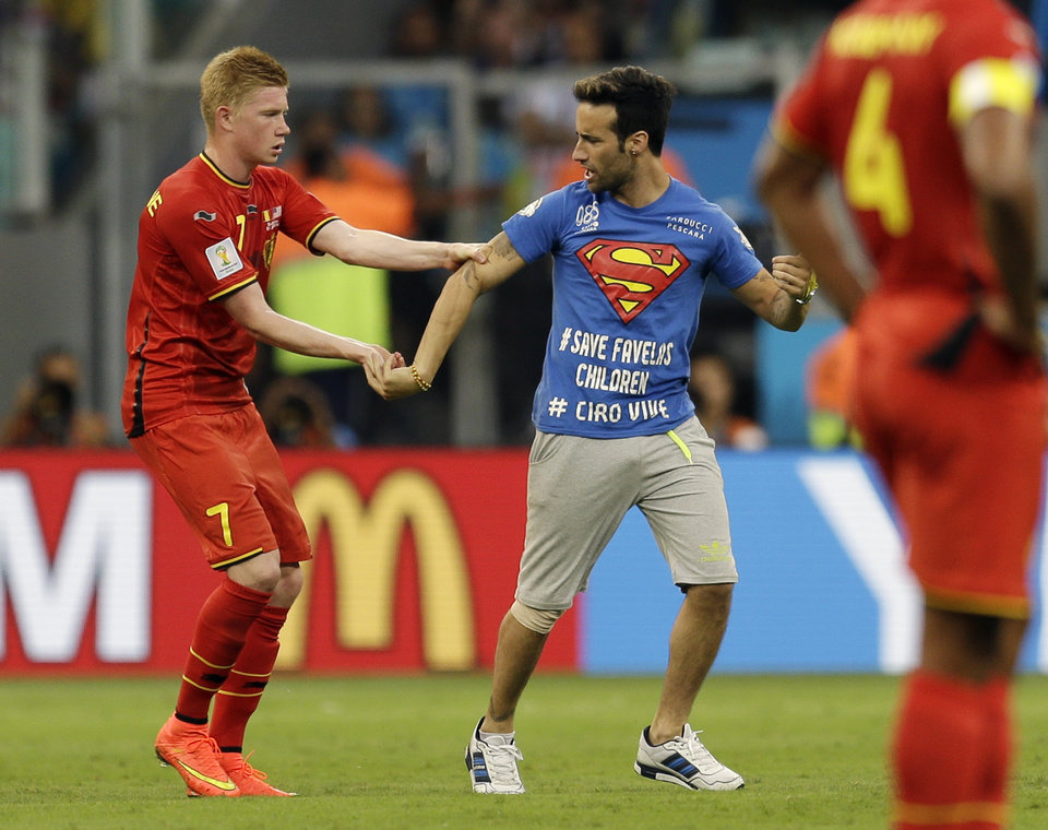 Photo - Belgium's Kevin De Bruyne holds on to a spectator who ran on to the pitch during the World Cup round of 16 soccer match between Belgium and the USA at the Arena Fonte Nova in Salvador, Brazil, Tuesday, July 1, 2014. (AP Photo/Natacha Pisarenko)