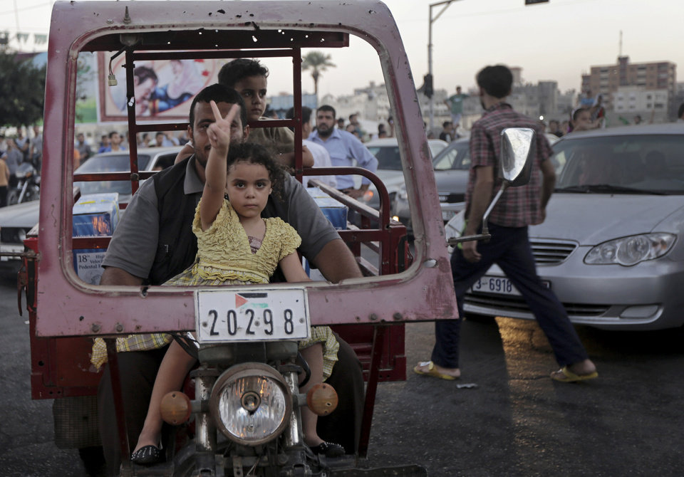 Photo - A Palestinian girl flashes victory sign with her father as they celebrate the cease-fire between Palestinians and Israelis at the main road in Gaza, in the northern Gaza Strip, Tuesday, Aug. 26, 2014.   Israel and Hamas agreed Tuesday to an open-ended cease-fire, halting a seven-week war that killed more than 2,200 people, the vast majority Palestinians, left tens of thousands in Gaza homeless and devastated entire neighborhoods in the blockaded territory.  (AP Photo/Adel Hana)