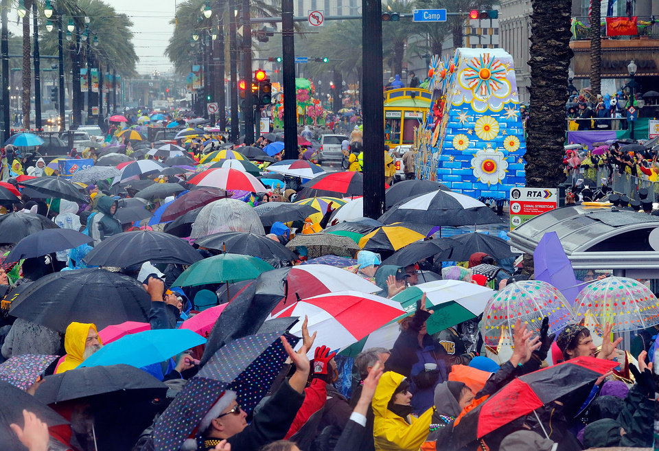 Photo - Wet revelers with umbrellas crowd along Canal Street during the Rex parade on Mardi Gras, Tuesday, March 4, 2014, in New Orleans. (AP Photo/NOLA.com The Times-Picayune, David Grunfeld) MAGS OUT; NO SALES; USA TODAY OUT; THE BATON ROUGE ADVOCATE OUT