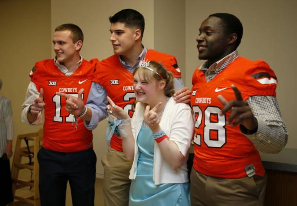 Photo - Krystal Littler gets a photo with Oklahoma State University football players Austin Hays, left, Mason Rudolph and James Washington, at right, during