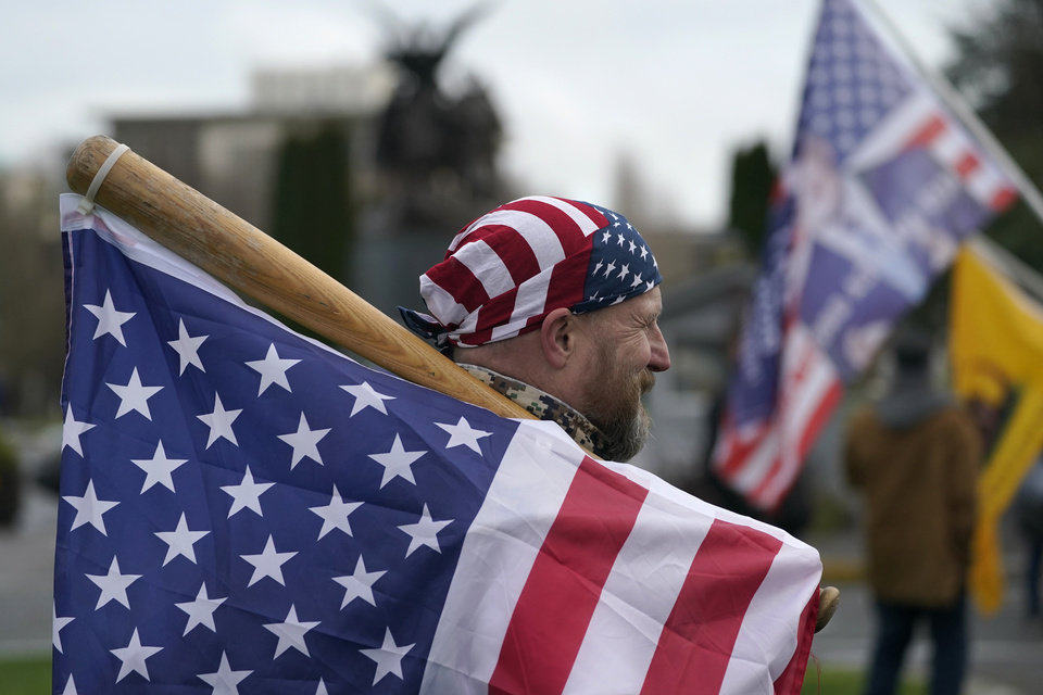 Photo - A man carries a U.S. flag attached to a baseball bat as he waits at the Capitol in Olympia, Wash., Wednesday, Jan. 6, 2021, before the start of a protest rally against the counting of electoral votes in Washington, DC, affirming President-elect Joe Biden's victory. People supporting President Donald Trump and other supporters began arriving at the Capitol mid-morning for a protest rally Wednesday that was expected to begin at noon. (AP Photo/Ted S. Warren)