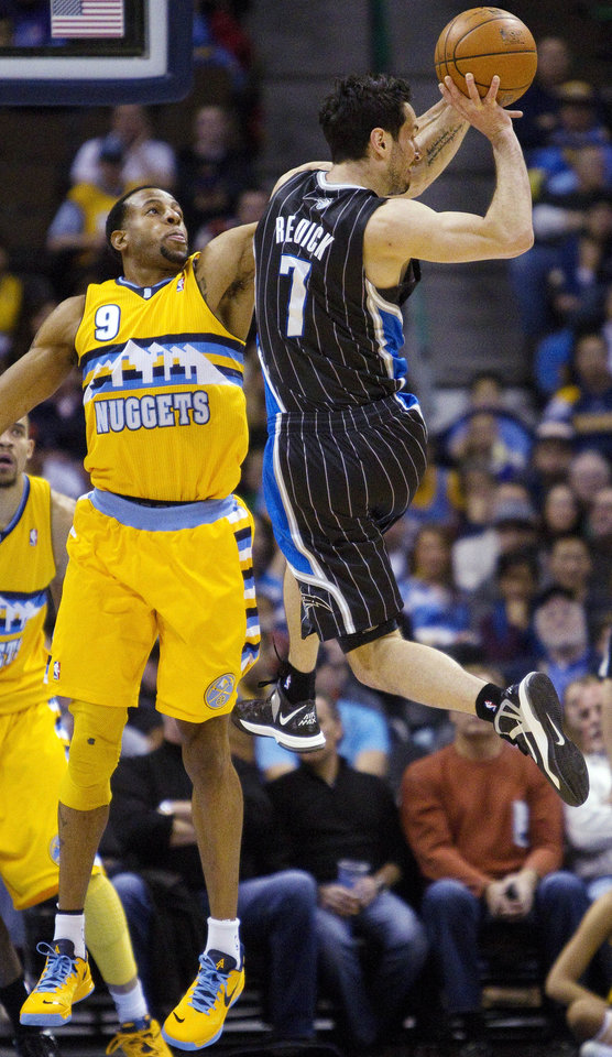 Denver Nuggets' Andre Iguodala (9) defends against a pass by Orlando Magic's J.J. Redick (7) during the first quarter of an NBA basketball game, Wednesday, Jan. 9, 2013, in Denver. (AP Photo/Barry Gutierrez)