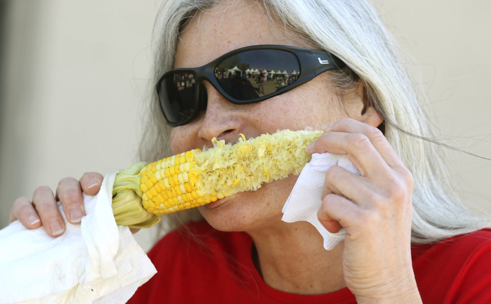 Photo - Sandy Pirrie eats corn on the cob during the 2014 Festival of the Arts in Oklahoma City, Tuesday April 22, 2014. Photo By Steve Gooch, The Oklahoman