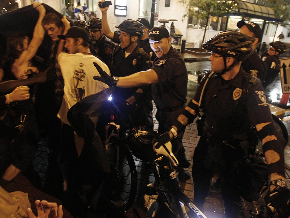 Photo - Occupy Demonstrators use a tarp to push against a police barricade during an unscheduled protest march, Tuesday, Sept. 4, 2012, in Charlotte, N.C. The Democratic National Convention begins today. (AP Photo/Gerry Broome) ORG XMIT: XDNC157