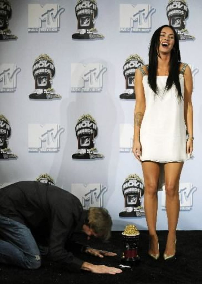 """Photo -  """"Transformers"""" director Michael Bay, left, bows down in front of cast member Megan Fox backstage after the film received the Best Movie award at the MTV Movie Awards in Los Angeles, Sunday, June 1, 2008. (AP Photo/Chris Pizzello)"""