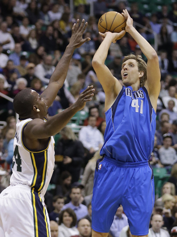 Photo - Dallas Mavericks forward Dirk Nowitzki (41) shoots as Utah forward Paul Millsap defends in the first quarter during an NBA basketball game Monday, Jan. 7, 2013, in Salt Lake City. (AP Photo/Rick Bowmer)