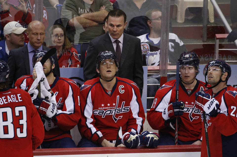 Photo - Washington Capitals head coach Adam Oates, top center, stands behind right wing Alex Ovechkin (8), from Russia, in the overtime portion of an NHL hockey game against the Tampa Bay Lightning, Sunday, April 13, 2014, in Washington. The Lightning won 1-0 in a shootout. (AP Photo/Alex Brandon)