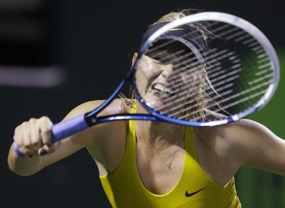 Photo - Maria Sharapova, of Russia, returns a shot from Lucie Safarova, of the The Czech Republic, during the Sony Open tennis tournament, Saturday, March 22, 2014, in Key Biscayne, Fla. (AP Photo/Wilfredo Lee)