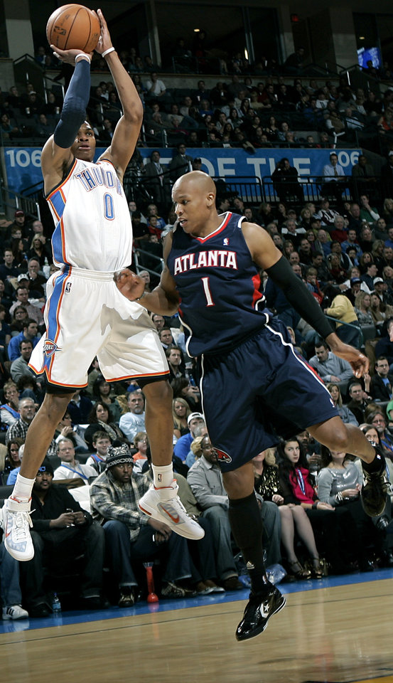 Photo - Oklahoma City's Russell Westbrook puts a shot over Atlanta's Maurice Evans during their NBA basketball game at the OKC Arena in Oklahoma City on Friday, Dec. 31, 2010. Photo by John Clanton, The Oklahoman