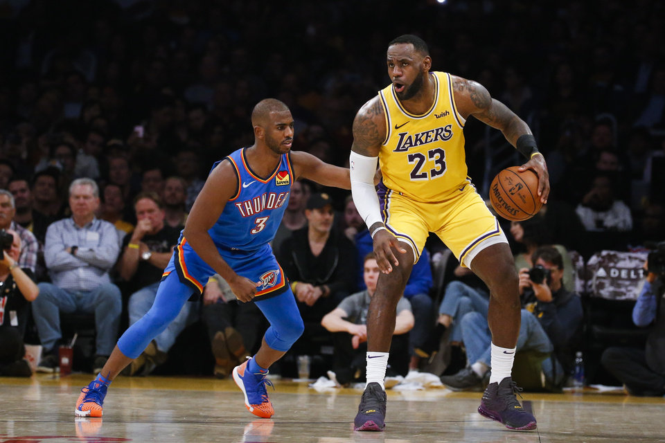 Photo - Los Angeles Lakers' LeBron James (23) dribbles against Oklahoma City Thunder's Chris Paul (3) during the second half of an NBA basketball game, Tuesday, Nov. 19, 2019, in Los Angeles. The Lakers won 112-107. (AP Photo/Ringo H.W. Chiu)