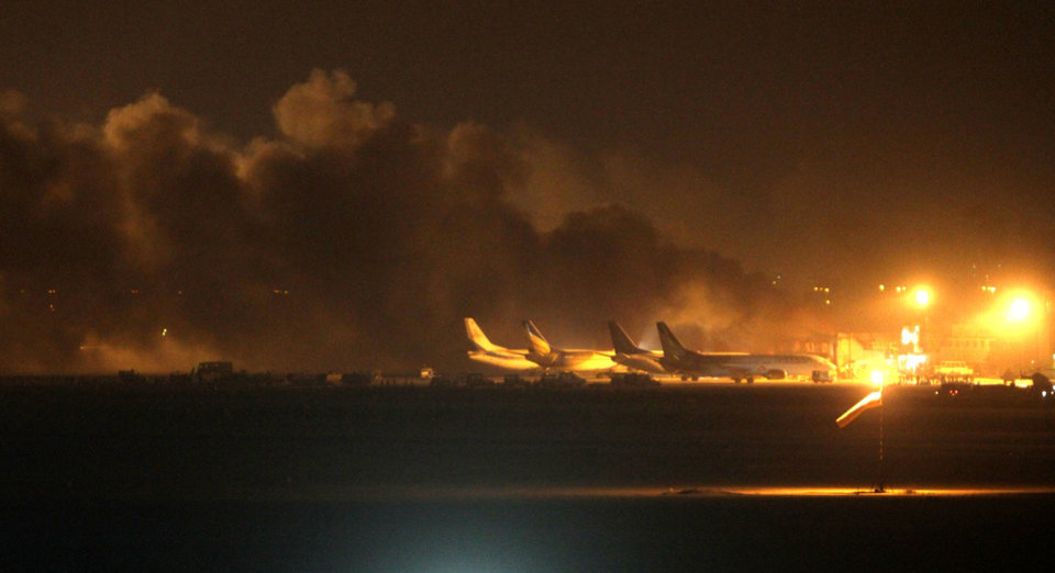 Photo - Fire illuminates the sky above the Jinnah International Airport in Karachi where security forces are fighting with attackers Sunday night, June 8, 2014, in Pakistan. Gunmen disguised as police guards attacked a terminal with machine guns and a rocket launcher during a five-hour siege that killed 13 people as explosions echoed into the night, while security forces retaliated and killed all the attackers, officials said Monday. (AP Photo/Fareed Khan)