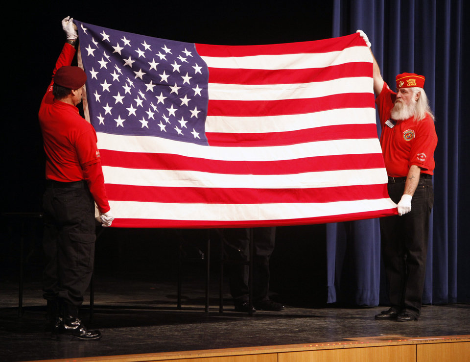Gary Hanson, left, and Terry Farmer demonstrate how to fold a flag during a patriotic flag folding demonstration and flag presentation at Southmoore High School.
