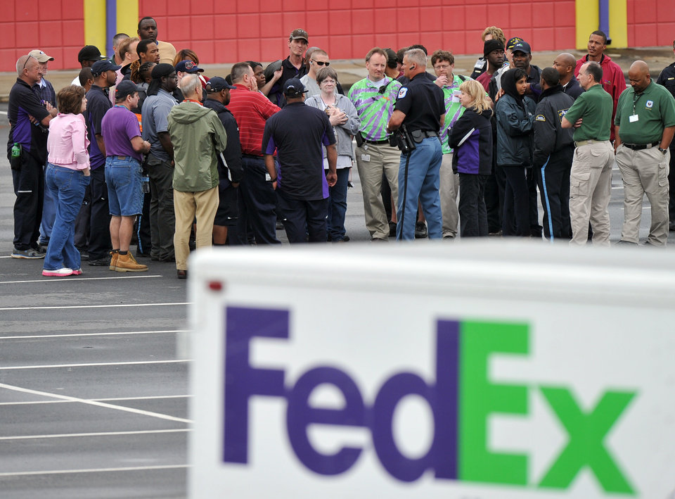 Photo - A Cobb County Police Officer speaks to FedEx employees and family members gathered at the parking lot of a skating rink located near the shipping facility where a gunman open fire in Kennesaw, Ga., on Tuesday, April 29, 2014.  A shooter described as being armed with an assault rifle and having bullets strapped across his chest