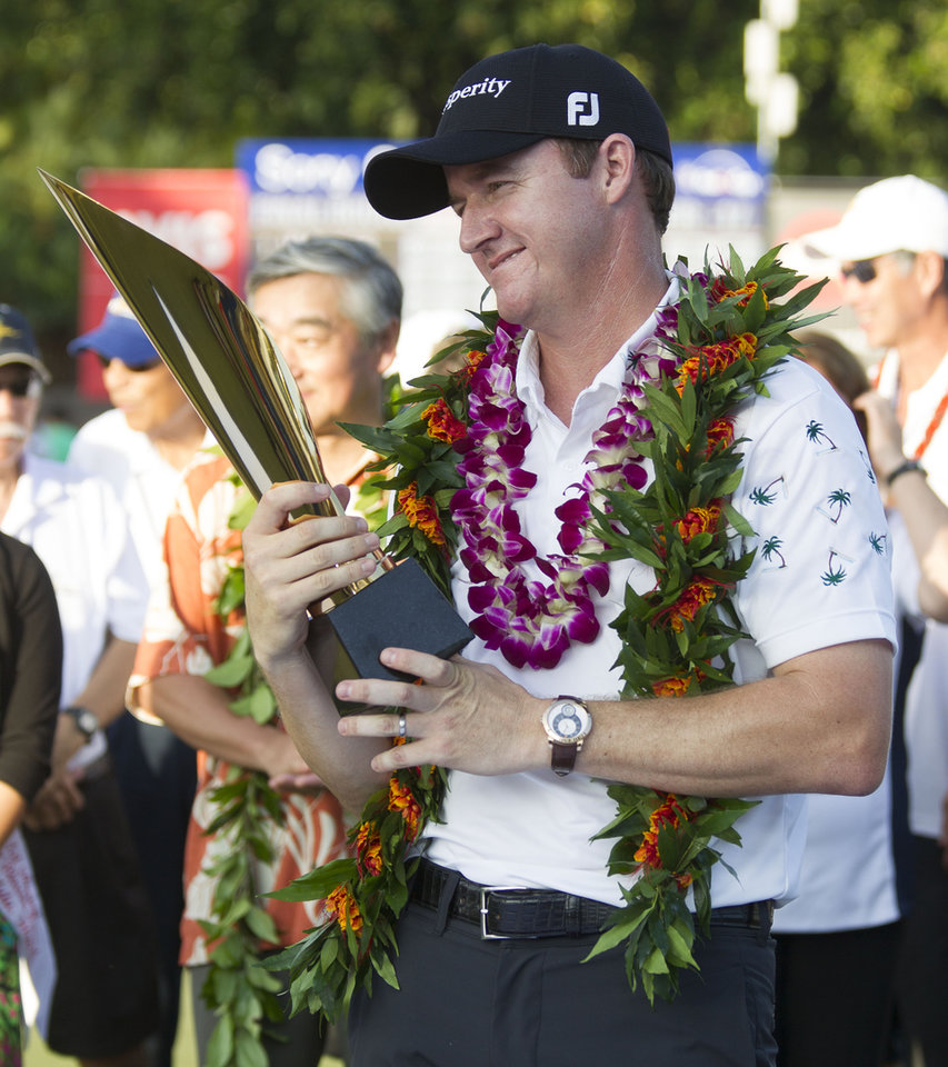 Photo - Jimmy Walker looks at the championship trophy after winning the Sony Open golf tournament at Waialae Country Club, Sunday, Jan. 12, 2014, in Honolulu. (AP Photo/Eugene Tanner)
