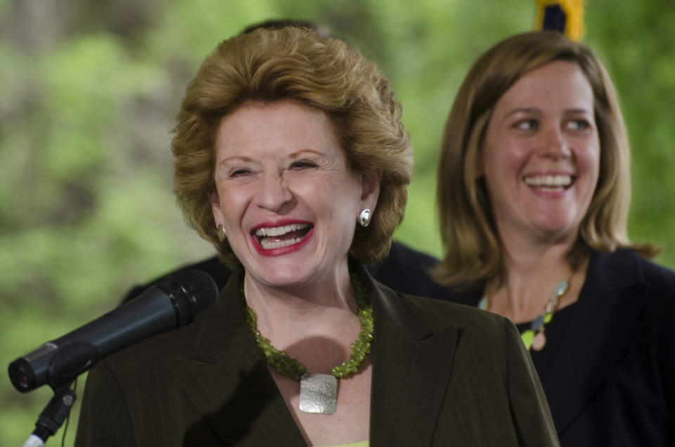 Photo - U.S. Sen. Debbie Stabenow laughs as she takes the podium during a press conference at the Bay City State Recreation Area in Bangor Township on Tuesday, May 27, 2014.  The U.S. Department of Agriculture is teaming with businesses, nonprofits and others on a five-year, $2.4 billion program that will fund locally designed soil and water conservation projects nationwide, Agriculture Secretary Tom Vilsack said.  Stabenow was primary writer of the farm bill with Rep. Frank Lucas of Oklahoma.  (AP Photo/The Bay City Times, Danielle McGrew)