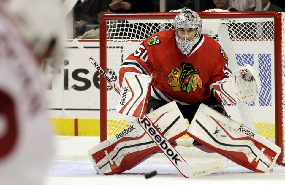 Photo - Chicago Blackhawks goalie Corey Crawford, right, saves a shot by Phoenix Coyotes' Shane Doan during the first period of an NHL hockey game in Chicago, Thursday, Nov. 14, 2013. (AP Photo/Nam Y. Huh)