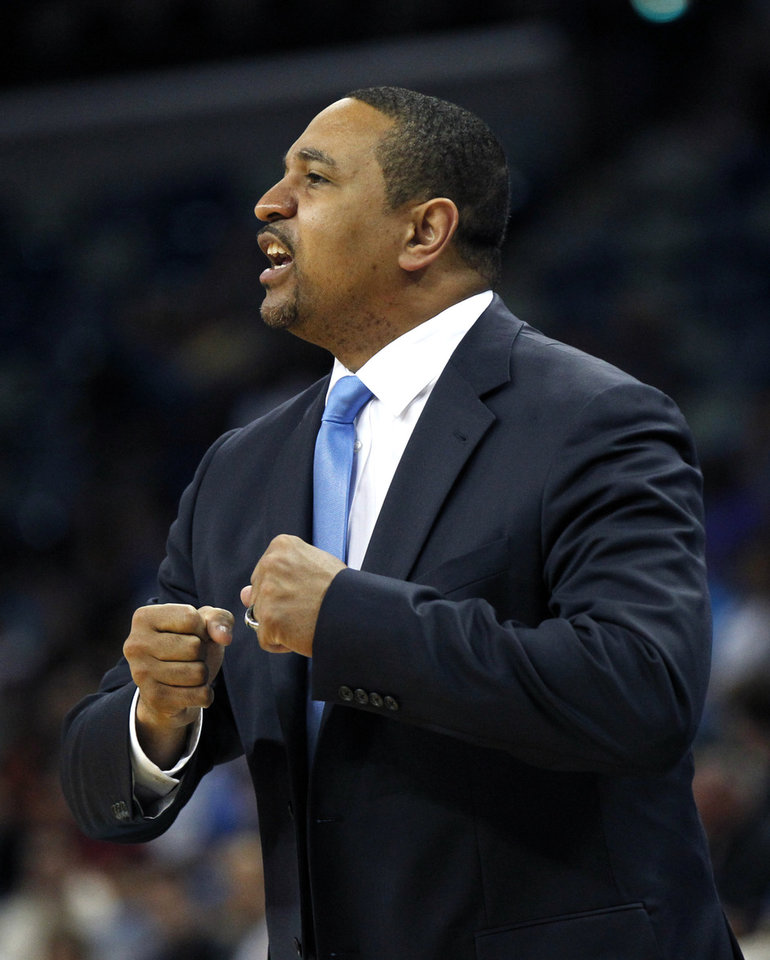 Photo - Golden State Warriors head coach Mark Jackson calls out to his team in the first half of an NBA basketball game against the New Orleans Hornets in New Orleans, Monday, March 18, 2013. (AP Photo/Gerald Herbert)