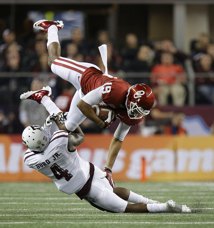Oklahoma\'s Justin Brown (19) is brought down by Texas A&M \'s Toney Hurd Jr. (4) during the Cotton Bowl college football game between the University of Oklahoma (OU)and Texas A&M University at Cowboys Stadium in Arlington, Texas, Friday, Jan. 4, 2013. Photo by Bryan Terry, The Oklahoman