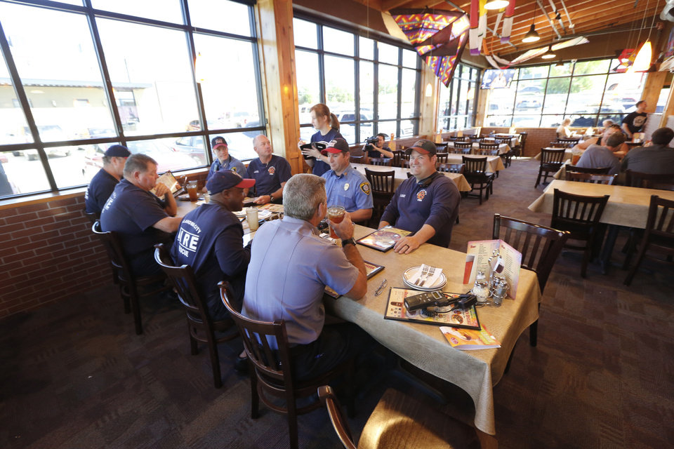 Photo - Oklahoma City firefighters enjoy lunch in the remodeled dinning room at Hideaway Pizza on North Western Avenue. The restaurant reopened Monday.  Steve Gooch - The Oklahoman