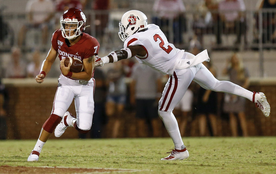 Photo - Oklahoma's Spencer Rattler (7) carries the ball past South Dakota's Mike Johnson (2) in the fourth quarter during a college football game between the Oklahoma Sooners (OU) and South Dakota Coyotes at Gaylord Family - Oklahoma Memorial Stadium in Norman, Okla., Saturday, Sept. 7, 2019. [Nate Billings/The Oklahoman]