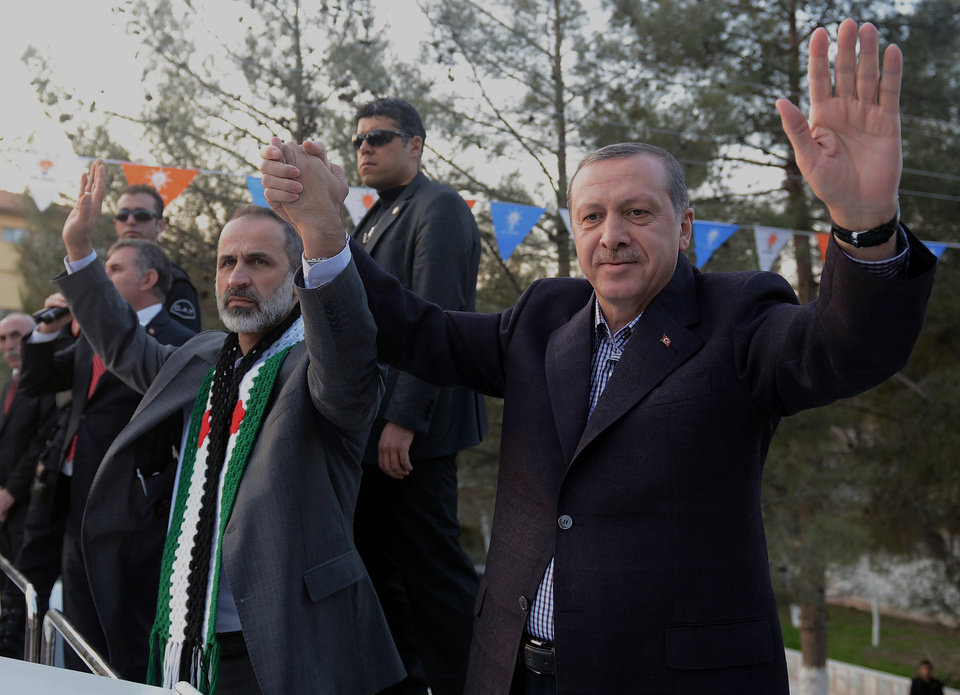 Photo - In this photo provided by Turkish Prime Minister's Press Service, Turkish Prime Minister Recep Tayyip Erdogan, right, flanked by the Syrian opposition coalition leader Mouaz al-Khatib, waves to people as he addresses residents of a Turkish village near the Syrian border, in Sanliurfa, Turkey, Sunday, Dec. 30, 2012. Erdogan repeated a call on Syrian President Bashar Assad to step down. (AP Photo/Kayhan Ozer)