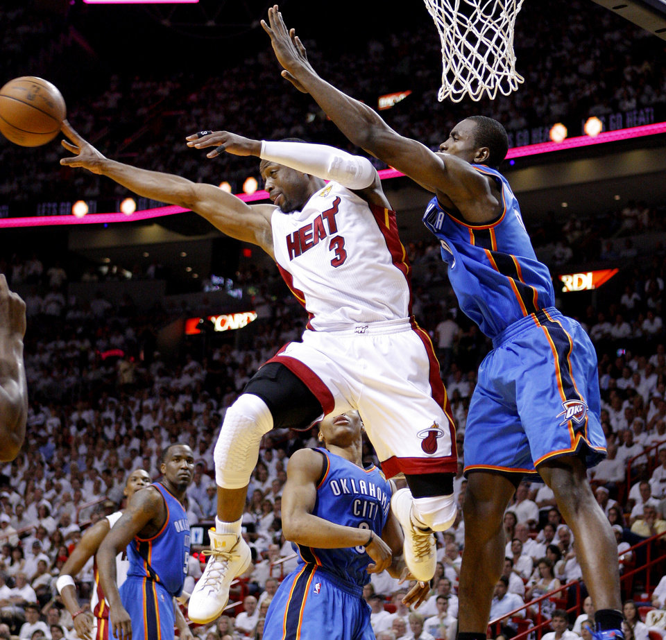 Photo - Miami's Dwyane Wade (3) goes past Oklahoma City's Serge Ibaka (9) during Game 5 of the NBA Finals between the Oklahoma City Thunder and the Miami Heat at American Airlines Arena, Thursday, June 21, 2012. Photo by Bryan Terry, The Oklahoman