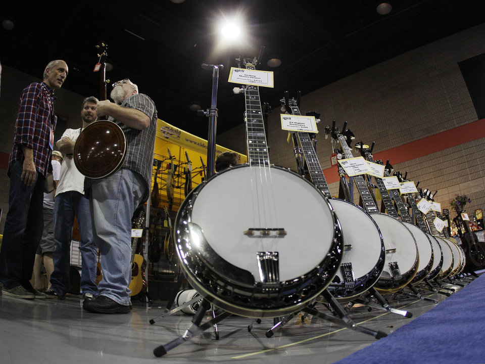 Musician Steve Cooley, front, examines one of the banjos on display on Tuesday, Sept. 27, 2011, during the week-long International Bluegrass Music Association celebration in Nashville, Tenn. (AP Photo/Mark Humphrey)