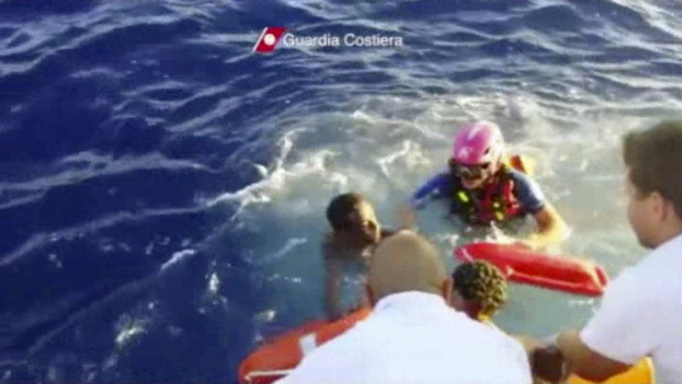 Photo - In this image made from video provided by the Italian Coast Guard and recorded on Thursday, Oct. 3, 2013, Italian Coast Guard rescue a survivor of a ship transporting hundreds of migrants which caught fire and sank off the Sicilian island of Lampedusa, Italy. Authorities on Friday, Oct. 4 are contending with choppy waters in the search for dozens of migrants believed to have drowned after their rickety boat caught fire and sank off the coast of the southern Italian island of Lampedusa. (AP Photo/Italian Coast Guard)