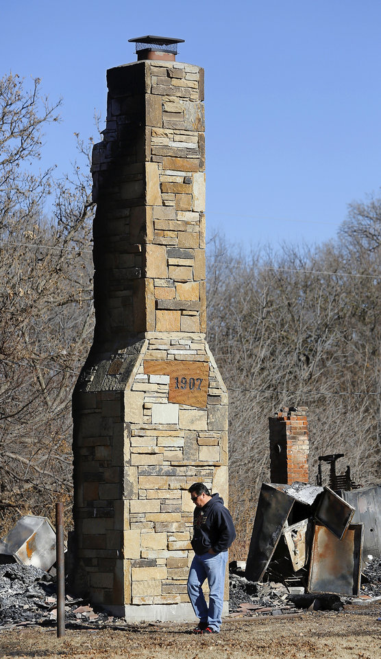 Chris Cochran walks past the stone chimney that stands above the charred rubble that was his  family's home in a rural area near Cashion until it was destroyed in a recent fire.  His son, Cayden Cochran, a star player when he attended Cashion High School, is now starting quarterback at Division II power Valdosta State, and this weekend, he leads Valdosta into the Division II national championship game. Photo taken Wednesday, Dec. 12, 2012.    Photo by Jim Beckel, The Oklahoman
