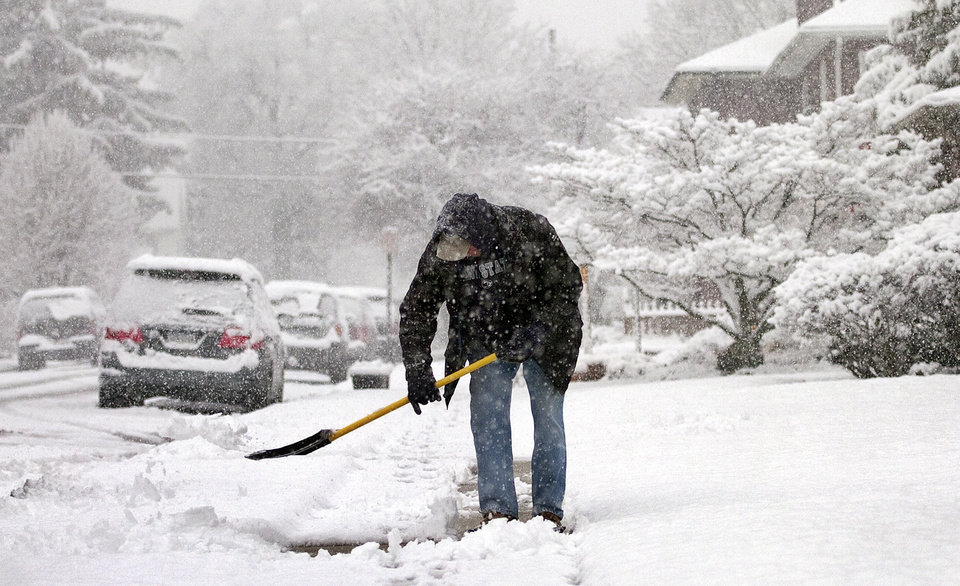 Ken Matthews clears snow from his sidewalk in front of his Spring Garden Township home in York County, Pa. on Monday, March 25, 2013. (AP Photo/York Dispatch, Jason Plotkin)  YORK DAILY RECORD OUT