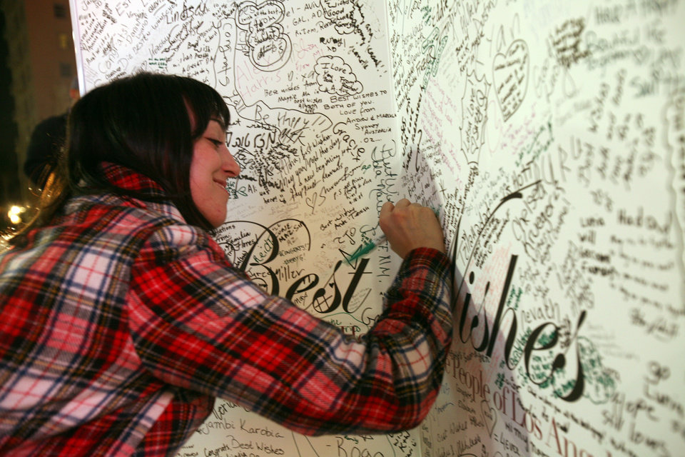 Photo - Royal enthusiast Julie Wenneker writes her wish on a giant card during a public celebration of the wedding of Prince William and Kate Middleton outside Madame Tussauds Hollywood in Los Angeles Friday April 29, 2011. (AP Photo/Ringo H.W. Chiu) ORG XMIT: CARC102