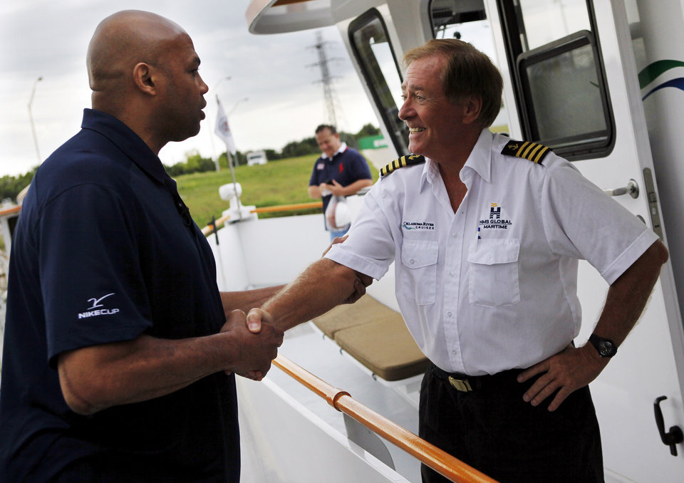 Photo - Charles Barkley, left, talks with Capt. Joe Harvey before taking an Oklahoma River Cruise in Oklahoma City, Friday, June 1, 2012. Barkley took the cruise on the Oklahoma River as part of a tour of Oklahoma City. Photo by Nate Billings, The Oklahoman