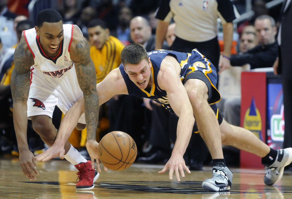 Atlanta Hawks point guard Jeff Teague, left, and Indiana Pacers power forward Tyler Hansbrough, right, vie for a loose ball during the first half of an NBA basketball game on Saturday, Dec. 29, 2012, at Philips Arena in Atlanta. (AP Photo/John Amis)