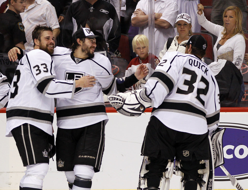 Photo -   Los Angeles Kings goalie Jonathan Quick (32) celebrates with teammates Willie Mitchell (33) and Drew Doughty during the third period of Game 5 of the NHL hockey Stanley Cup Western Conference finals, Tuesday, May 22, 2012, in Glendale, Ariz. The Kings won 4-3 in overtime. (AP Photo/Matt York)