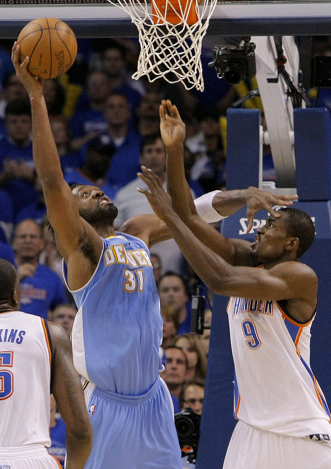 Photo - Oklahoma City's Serge Ibaka (9) battles with Denver's Nene (31) under the basket during the first round NBA playoff game between the Oklahoma City Thunder and the Denver Nuggets on Sunday, April 17, 2011, in Oklahoma City, Okla. Photo by Chris Landsberger, The Oklahoman