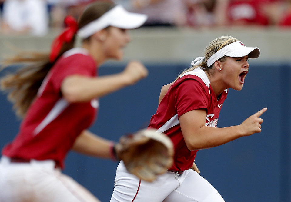 Photo - Oklahoma's Georgia Casey (42) and Oklahoma's Jessica West (27) celebrate a out during Women's College World Series softball game between Oklahoma and Tennessee at ASA Hall of Fame Stadium in Oklahoma City,Tuesday, June, 4, 2013. Photo by Sarah Phipps, The Oklahoman