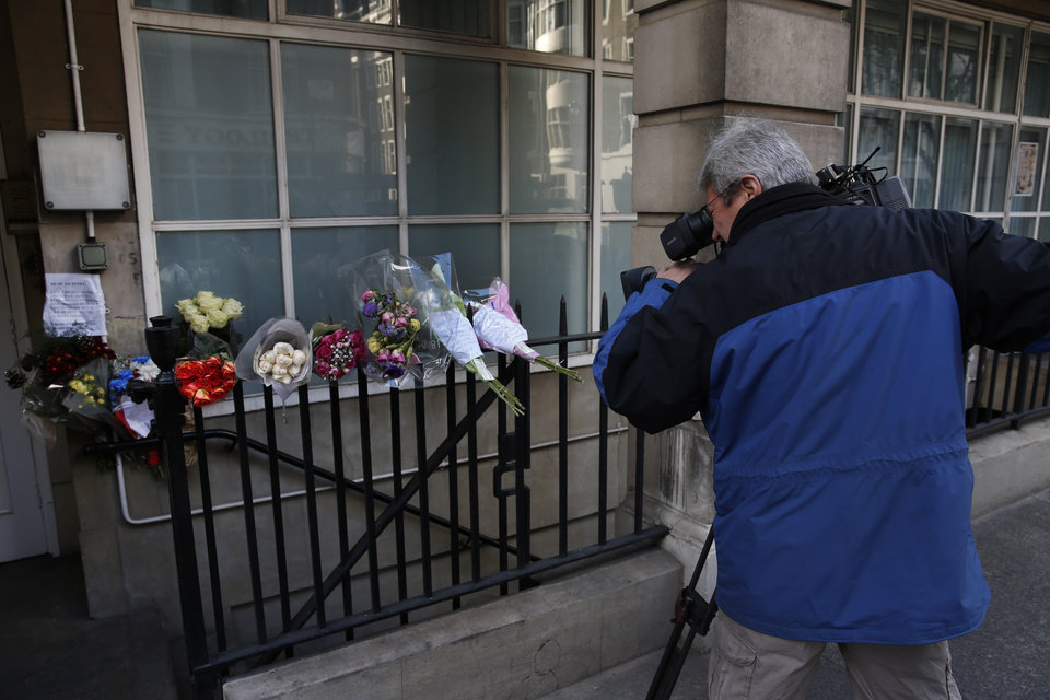 Photo - A news cameraman films flower tributes to late nurse Jacintha Saldanha outside the residential apartments of the the King Edward VII hospital where she was found dead, in central London, Monday, Dec. 10, 2012. Australian radio hosts managed to impersonate Queen Elizabeth II and Prince Charles and received confidential information about the Duchess of Cambridge's medical condition, in a hoax phone call to the hospital where the pregnant Duchess was staying and which was broadcast on-air. The controversial prank took a dark twist three days later with the death of Saldanha, a 46-year-old mother of two, who was duped by the DJs despite their Australian accents. (AP Photo/Lefteris Pitarakis)